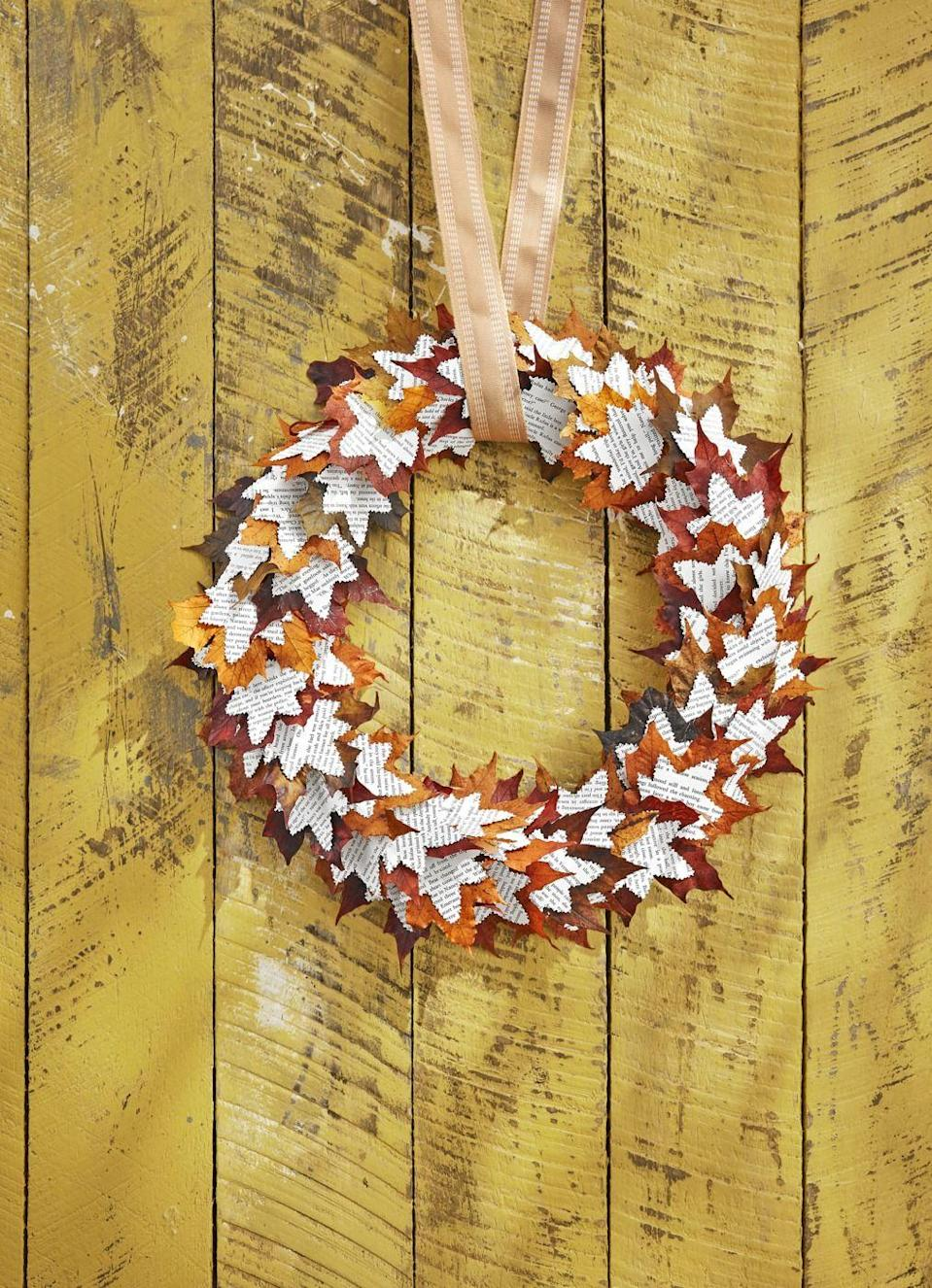 """<p>How fun is this paper wreath? Allow it to bring the spirit of fall right to your front door this year.</p><p><strong>Make the wreath:</strong> Draw a 3-inch-wide maple leaf shape on a piece of cardboard and cut out to create a stencil. Trace on original pages (or, preferred, photocopied pages) of a vintage book—consider a fall-themed title or mystery novel—and cut out approximately 100 leaves with decorative scissors that have a """"torn paper"""" edge. Attach book page leaves to maple leaves with hot glue. Attach layered leaves to a 16-inch wreath form with hot glue, layering and overlapping them as you go. Hang with burlap ribbon. </p>"""