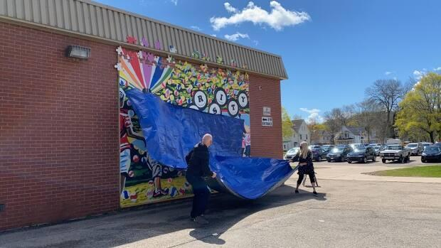 The mural being revealed at Sussex Elementary School.