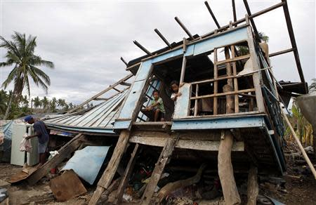 Typhoon victims look out from their house that was damaged by Super Typhoon Haiyan in Bogo, Cebu in central Philippines November 17, 2013. REUTERS/Erik De Castro