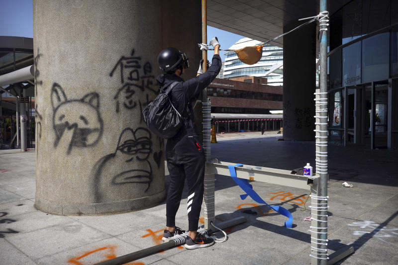A protester works on a homemade slingshot at Hong Kong Polytechnic University in Hong Kong, Friday, Nov. 15, 2019. Protesters who barricaded themselves inside Hong Kong's universities have tried to turn the campuses into armed camps, resorting to medieval weapons to stop police from entering the grounds. Their weapons include bows and arrows, catapults and hundreds of gasoline bombs stacked up to ramparts - often built by the students. (AP Photo/Vincent Yu)