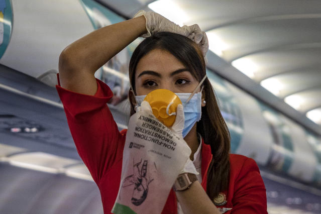 A flight attendant is pictured wearing a mask and gloves while demonstrating safety procedures on a flight bound for Manila in the Philippines on 10 March. (Getty Images)
