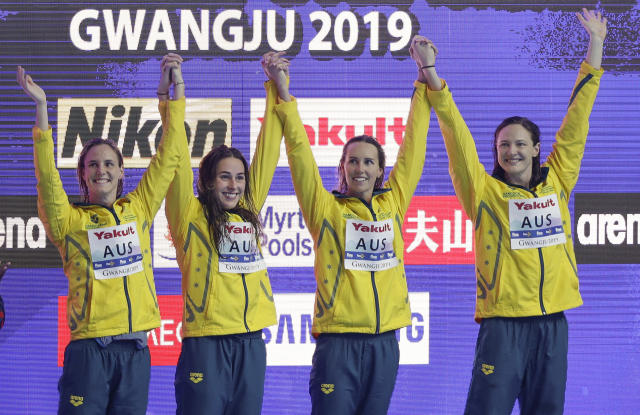 Australia women's 4x100m relay team wave as they stand on the podium to receive their gold medals at the World Swimming Championships in Gwangju, South Korea, Sunday, July 21, 2019. (AP Photo/Mark Schiefelbein)