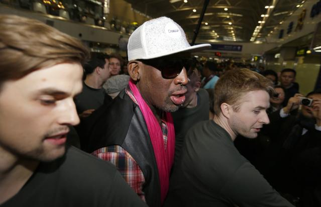 Former NBA basketball player Dennis Rodman is protected by staff members as he arrives at the Beijing Capital International Airport to leave for Pyongyang, in Beijing
