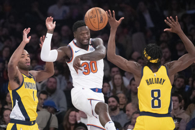 New York Knicks forward Julius Randle (30) moves the ball around Indiana Pacers forwards Justin Holiday (8) and T.J. Warren (1) in the first half of an NBA basketball game, Friday, Feb. 21, 2020, at Madison Square Garden in New York. (AP Photo/Mary Altaffer)