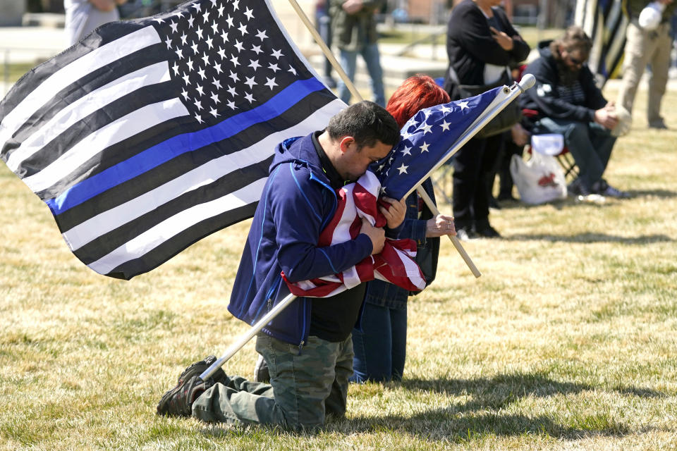 Marius Annandale kneels while praying during a Second Amendment rally at the Utah State Capitol Saturday, March 27, 2021, in Salt Lake City. (AP Photo/Rick Bowmer)