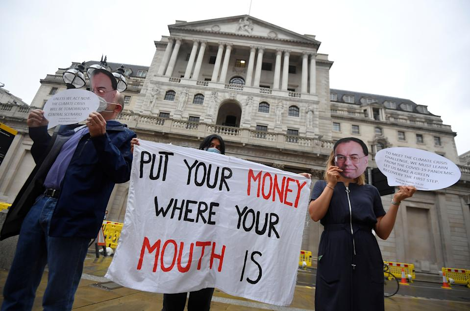 Environmental activists wear face masks depicting governor Andrew Bailey, during a protest to encourage green economy, outside the Bank of England in the City of London, on 6 August 2020. Photo: Toby Melville/Reuters