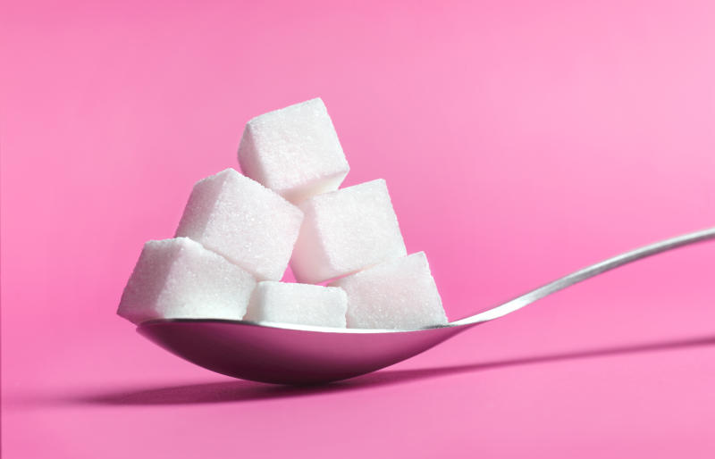Close up of a spoon pilled high with sugar cubes on pink background