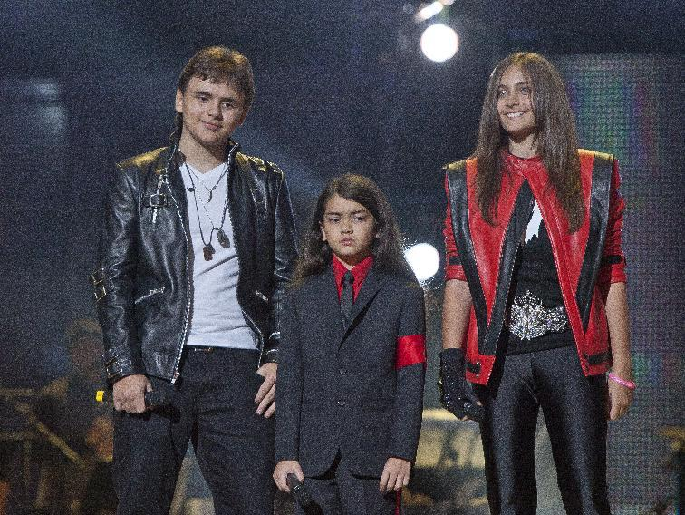 """FILE - In this Oct. 8, 2011 file photo, from left, Prince Jackson, Prince Michael II """"Blanket"""" Jackson and Paris Jackson arrive on stage at the Michael Forever the Tribute Concert, at the Millennium Stadium in Cardiff, Wales. The children's cousin and co-guardian, TJ Jackson, described their lives and the difficulty they have grieving due to paparazzi scrutiny to a jury hearing a lawsuit against AEG Live LLC on Thursday, June 27, 2013, in Los Angeles. (AP Photo/Joel Ryan, File) *Editorial Use Only*"""