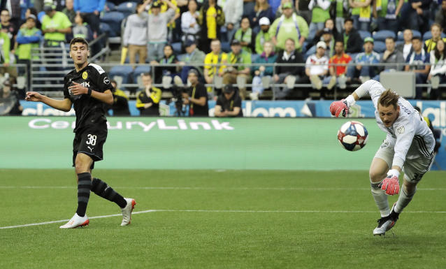 FILE - In this Wednesday, July 17, 2019 file photo, Borussia Dortmund's Gio Reyna, left, reacts after missing a shot against Seattle Sounders goalkeeper Bryan Meredith during a friendly soccer match, in Seattle. Gio Reyna, already the youngest American to play in the Bundesliga, is making his first league start for Borussia Dortmund in the Ruhr derby against visiting Schalke. The 17-year-old Reyna was named in coach Lucien Favres starting lineup alongside fellow youngster Erling Haaland on Saturday, May 16, 2020 when the league resumes after a two-month break caused by the coronavirus. (AP Photo/Ted S. Warren, file)