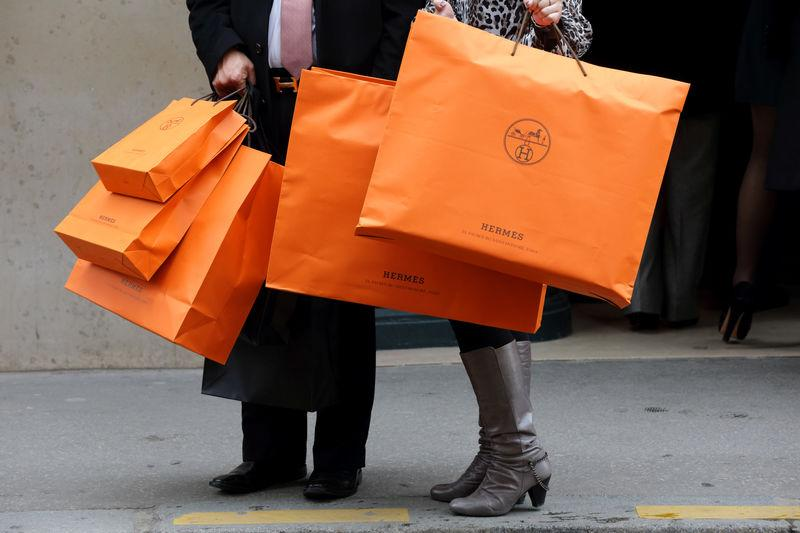 FILE PHOTO: A couple walk with Hermes shopping bags as they leave a Hermes store in Paris