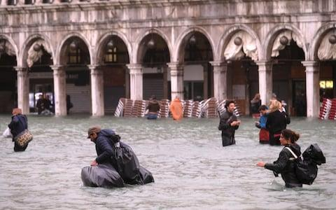 Residents and visitors were wading through waist-high water in St Mark's Square before the mayor gave orders to evacuate the area - Credit: REUTERS