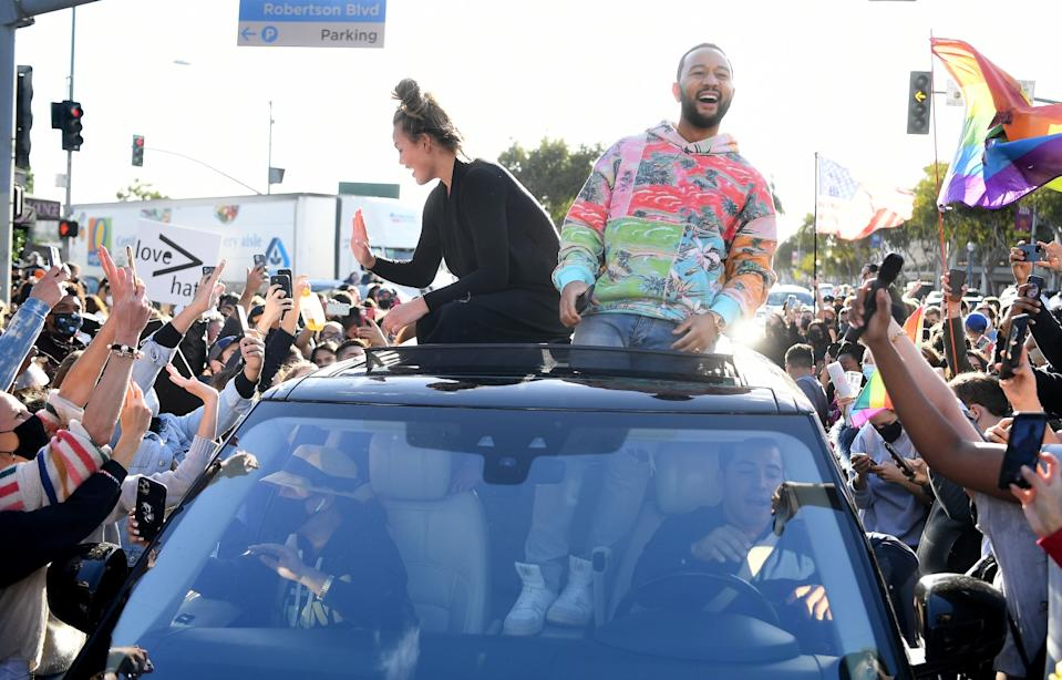 John Legend and Chrissy Teigen celebrate from a car's sunroof on Santa Monica Boulevard in West Hollywood.