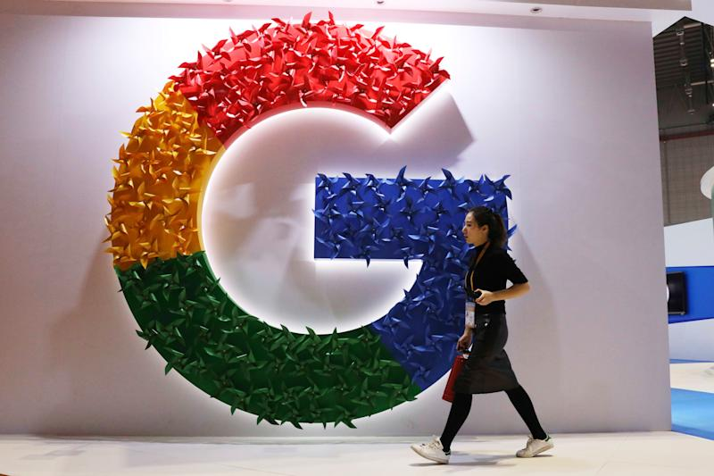 FILE - In this Monday, Nov. 5, 2018 file photo, a woman walks past the logo for Google at the China International Import Expo in Shanghai. Google says it will start giving European Union smartphone users a choice of browsers and search apps on its Android operating system. The changes are designed to comply with an EU antitrust ruling. The U.S. internet giant said Thursday, April 18, 2019 that following an Android update, users will be shown two new screens giving them the option install up to five search apps and five browsers. (AP Photo/Ng Han Guan)