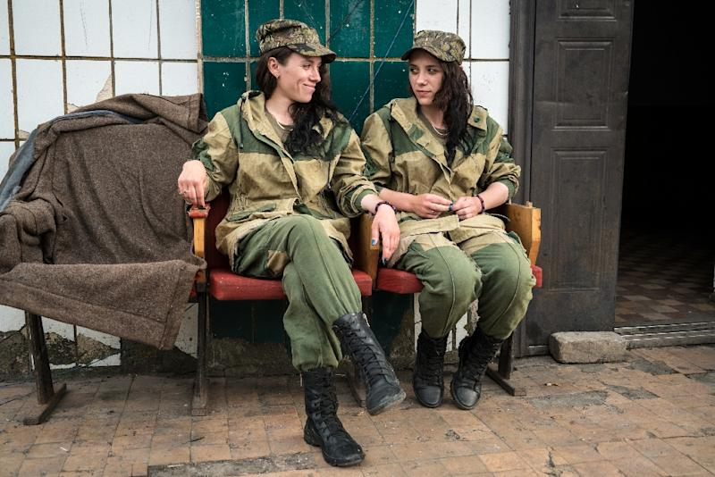 Pro-Russian separatists, twin sisters Anya (R) and Katya pose for a photo near Telmonove, Donetsk region (AFP Photo/Andrey Borodulin)