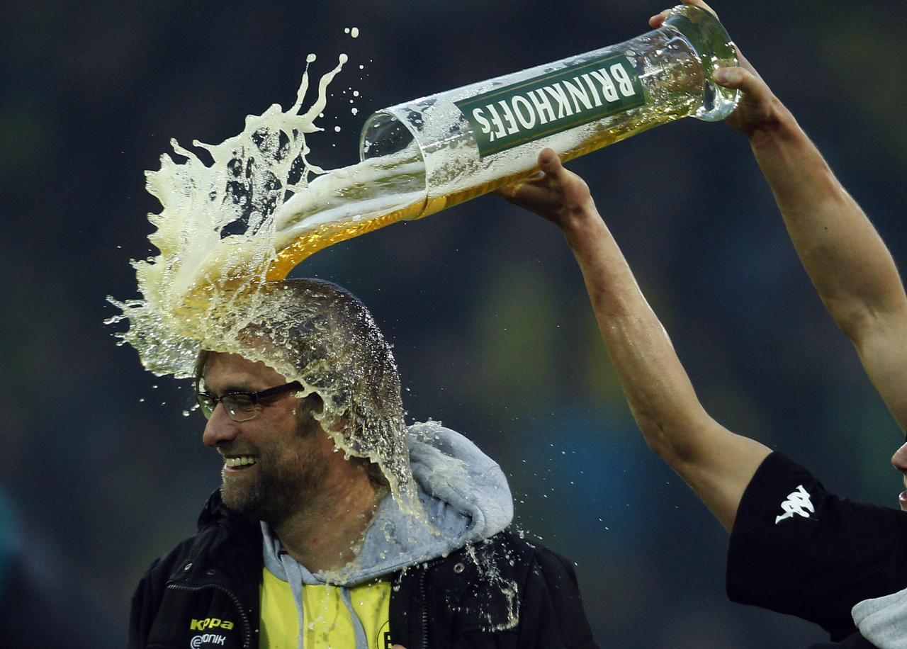 Borussia Dortmund's Lukasz Piszczek (R) pours a glass a beer over his coach Juergen Klopp after winning the German Championship following their German first division Bundesliga soccer match against Borussia Moenchengladbach in Dortmund April 21, 2012. Borussia Dortmund won the Bundesliga for the second year running on Saturday, clinching the title with a 2-0 win over Borussia Moenchengladbach. REUTERS/Ina Fassbender (GERMANY - Tags: SPORT SOCCER TPX IMAGES OF THE DAY) DFL LIMITS USE OF IMAGES ON THE INTERNET TO 15 PICTURES DURING THE MATCH AND, PROHIBITS MOBILE (MMS) USE DURING AND UP TO 2 HOURS POST MATCH. FOR MORE INFORMATION CONTACT DFL