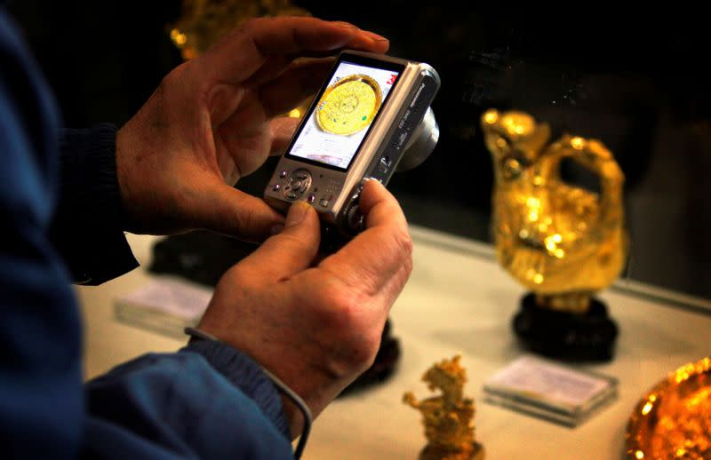 FILE PHOTO: A man takes a photo of gold miniature statues and plates on display at a Chinese cultural fair in Beijing
