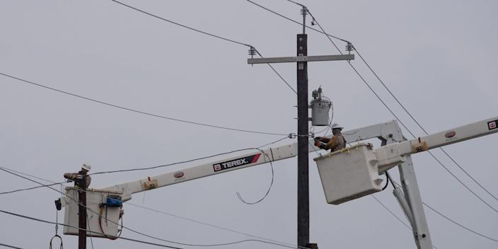 Electrical power-line installers make repairs in the aftermath of Hurricane Hanna in Port Mansfield, Texas, on July 26, 2020.