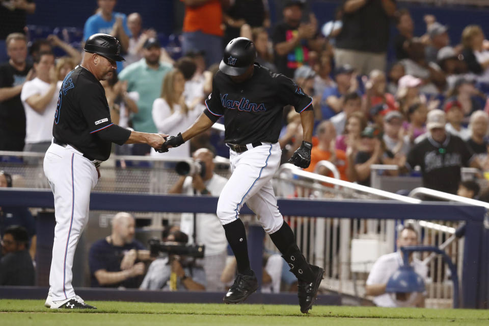 Miami Marlins' Curtis Granderson, right, is congratulated by third base coach Fredi Gonzalez (33) after hitting a solo home run during the eight inning of a baseball game against the Atlanta Braves, Saturday, Aug. 10, 2019, in Miami. (AP Photo/Brynn Anderson)