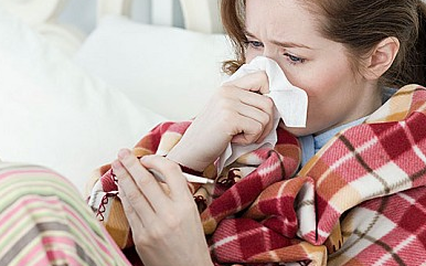 A woman lies in bed with the flu - Credit: Alamy