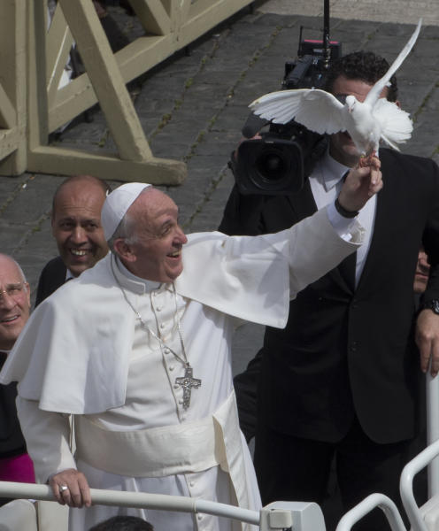 Pope Francis frees a dove during his weekly general audience in St. Peter Square at the Vatican, Wednesday, May 15, 2013. As Francis toured the square in his open-topped popemobile at his Wednesday audience with the public, someone at the edge of the crowd thrust a white bird cage at him. Looking puzzled, his security detail took the cage, containing a pair of white doves, and handed it to Francis. Without hesitation, the pope opened the cage door, thrust a hand inside and extracted one dove, and with a flick of his hand, sent the bird flying over the square. (AP Photo/Alessandra Tarantino)