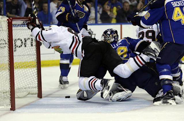 Chicago Blackhawks' Marian Hossa, of Slovakia, scores past St. Louis Blues goalie Ryan Miller, right, during the first period in Game 5 of a first-round NHL hockey playoff series Friday, April 25, 2014, in St. Louis. (AP Photo/Jeff Roberson)