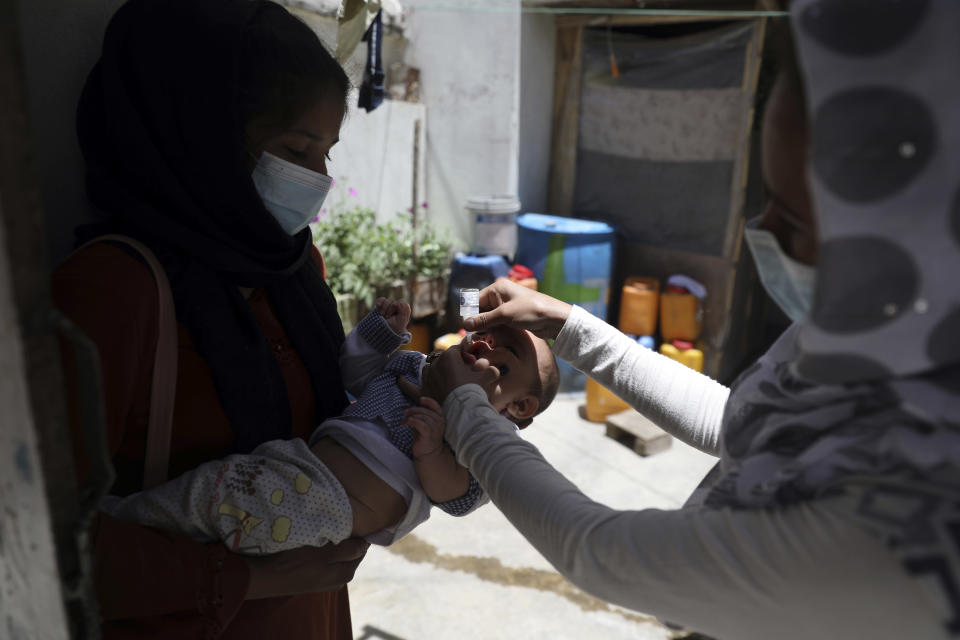 A health worker administers a vaccination to a child during a polio campaign in the old part of Kabul, Afghanistan, Tuesday, June 15, 2021. Gunmen on Tuesday targeted members of polio teams in eastern Afghanistan, killing a number of staffers, officials said. (AP Photo/Rahmat Gul)
