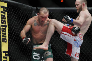 TJ Grant knees Gray Maynard during their fight. (USA Today)