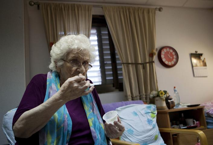 In this photograph made on Tuesday, Oct. 30, 2012, Rivke Holop, 85, eats medical cannabis at the old age nursery home in kibbutz Naan next to the city of Rehovot, Israel. Marijuana is illegal in Israel but medical use has been permitted since the early nineties for cancer patients and those with pain-related illnesses such as Parkinson's, Multiple Sclerosis, and even post-traumatic stress disorder. (AP Photo/Dan Balilty)