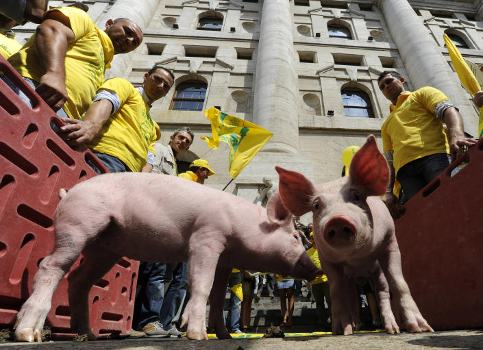 Protesters look at pigs during a protest, organized by the farmer's trade union Coldiretti in front of the Milan's stock exchange July 26, 2011. The farmer's union protested against international speculation of raw material that has caused the increase in price of the animal feed, and they urged the government to protect them. (REUTERS/Paolo Bona)