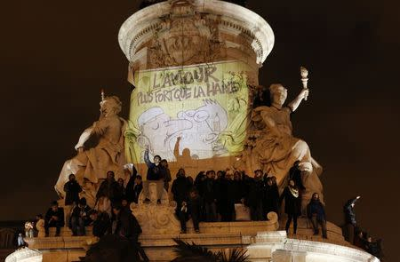 """A sign reading """"Love is stronger than hate"""" is projected at Republique square as people attend a vigil to pay tribute to the victims of a shooting by gunmen at the offices of weekly satirical magazine Charlie Hebdo in Paris January 7, 2015. REUTERS/Youssef Boudlal"""