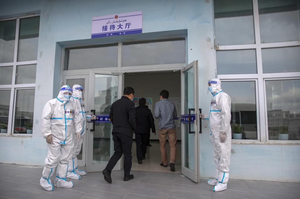 Security officers in protective suits hold the doors as government officials enter the visitors' hall at the Urumqi No. 3 Detention Center in Dabancheng in western China's Xinjiang Uyghur Autonomous Region on April 23, 2021. (AP Photo/Mark Schiefelbein)