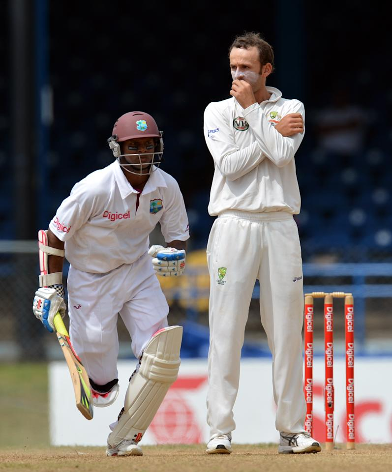Australian bowler Nathan Lyon (R) watches as West Indies batsman Shivnarine Chanderpaul (L) runs for two during the third day of the second-of-three Test matches between Australia and West Indies April 17, 2012 at Queen's Park Oval in Port of Spain, Trinidad. AFP PHOTO/Stan HONDA (Photo credit should read STAN HONDA/AFP/Getty Images)