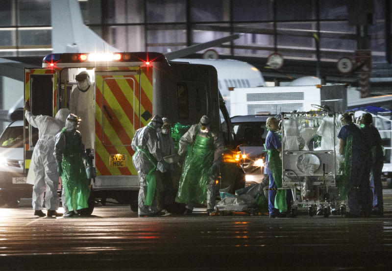 A healthcare worker (C) diagnosed with Ebola after returning from Sierra Leone is walked from an ambulance and put into a quarantine tent before being wheeled into a plane at Glasgow International Airport on December 30, 2014