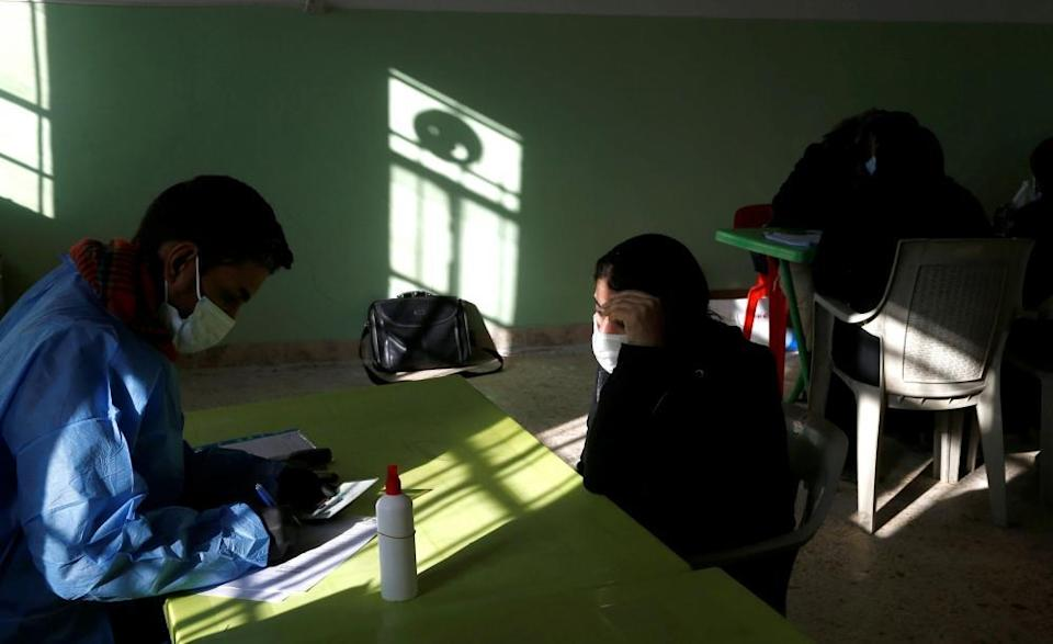 An employee from the Martyrs' Foundation fills out a missing persons form for a Yazidi woman looking for a relative missing after the August 2014 Isis attack in Kocho.