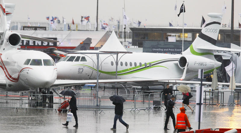 Visitors walk past Dassault Falcon jets during the first day of the Paris Air Show at Le Bourget airport, north of Paris, Monday June 17, 2013.(AP Photo/Remy de la Mauviniere)