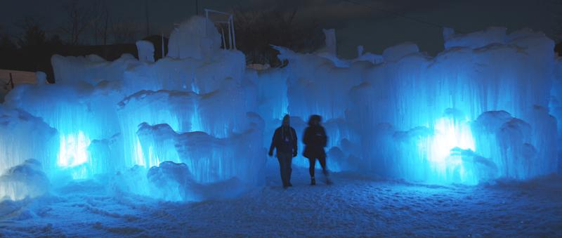 In this photo taken Wednesday Jan. 8, 2014 patrons tour an ice castle at the base of the Loon Mountain ski resort in Lincoln, N.H. The ice castle begins to grow in the fall when the weather gets below freezing and thousands of icicles are made and harvested then placed around sprinkler heads and sprayed with water. The castle will continue to grow as long as the temperatures stay below freezing.(AP Photo/Jim Cole)