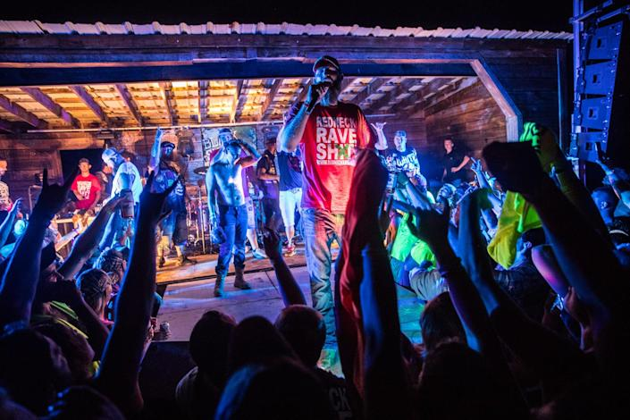 Redneck Rave creator and music artist Justin Stowers performs with other country rap artists during the Redneck Rave at BlackSwan Mudpit in Medora, Ind., on July 20, 2018. Stowers, a self proclaimed city-boy from Fort Wayne, started the Redneck Rave in 2016. The event has since moved slightly south to Kentucky.