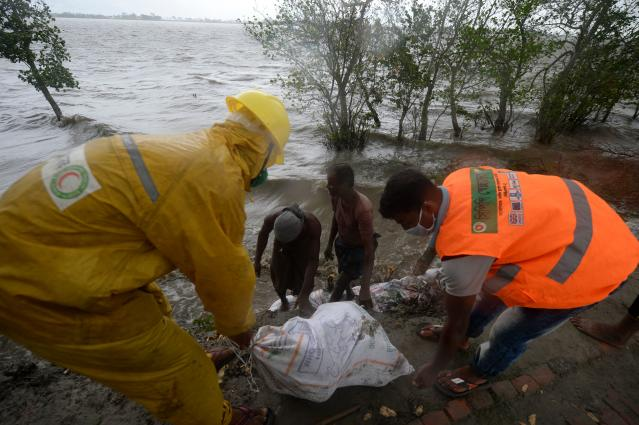 """Workers and villagers reinforce an embankment with sacks of soil ahead of the expected landfall of cyclone Amphan, in Dacope on May 20, 2020. - Several million people were taking shelter and praying for the best on Wednesday as the Bay of Bengal's fiercest cyclone in decades roared towards Bangladesh and eastern India, with forecasts of a potentially devastating and deadly storm surge. Authorities have scrambled to evacuate low lying areas in the path of Amphan, which is only the second """"super cyclone"""" to form in the northeastern Indian Ocean since records began. (Photo by Munir Uz zaman / AFP) (Photo by MUNIR UZ ZAMAN/AFP via Getty Images)"""