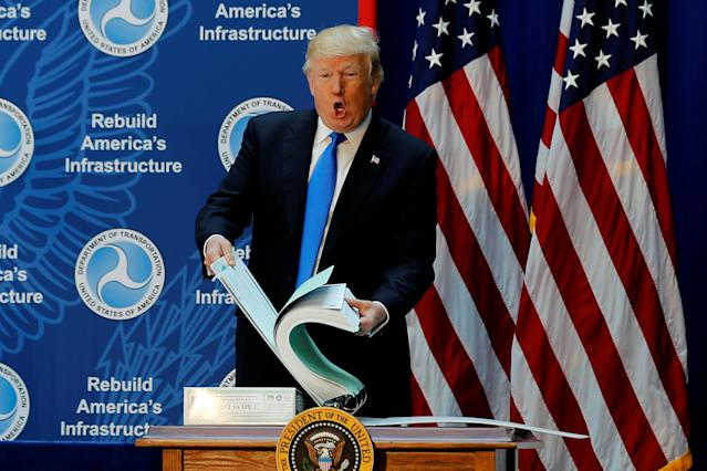 "<span class=""s1"">President Trump shows off a binder with highway permitting documents while discussing infrastructure improvements on June 9. (Photo: Jonathan Ernst/Reuters)</span>"