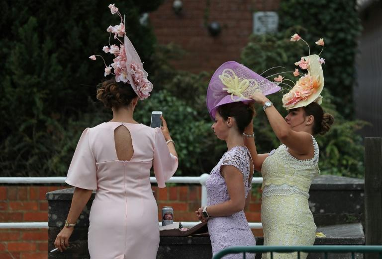 Immaculately-dressed racegoers help each other with their hats on arrival