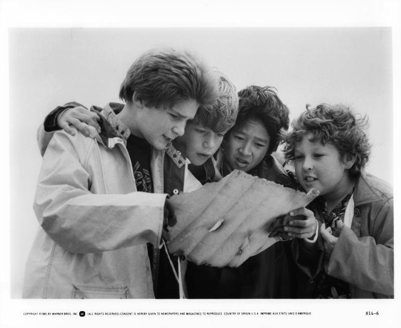 From left to right, Corey Feldman, Sean Astin, Ke Huy Quan and Jeff Cohen reading a treasure map in a scene from the film 'Goonies', 1985. (Photo by Warner Brothers/Getty Images)