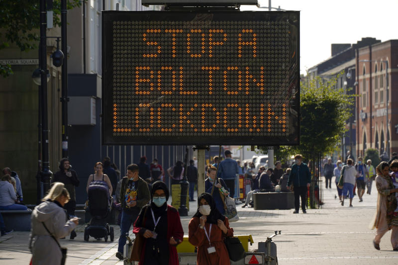 BOLTON, ENGLAND - SEPTEMBER 17: People walk past an electronic sign displaying health advice about COVID-19 on September 17, 2020 in Bolton, England. Fears about rising infection rates among younger people across the Uk has forced the government into tighter lockdown restrictions, particularly in the North of England. (Photo by Christopher Furlong/Getty Images)