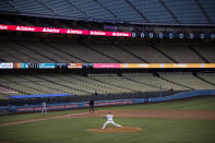 FILE - In this July 26, 2020, file photo, with the seats in Dodger Stadium empty, Los Angeles Dodgers starting pitcher Julio Urias throws the ball to a San Francisco Giants batter during the third inning of a baseball game in Los Angeles. Los Angeles and San Francisco are poised Tuesday, May 4, to be the only major urban areas in the state to meet guidelines to move into the least-restrictive tier. It's a remarkable turnaround considering California was the epicenter of the virus outbreak in the U.S. just a few months earlier. (AP Photo/Jae C. Hong, File)