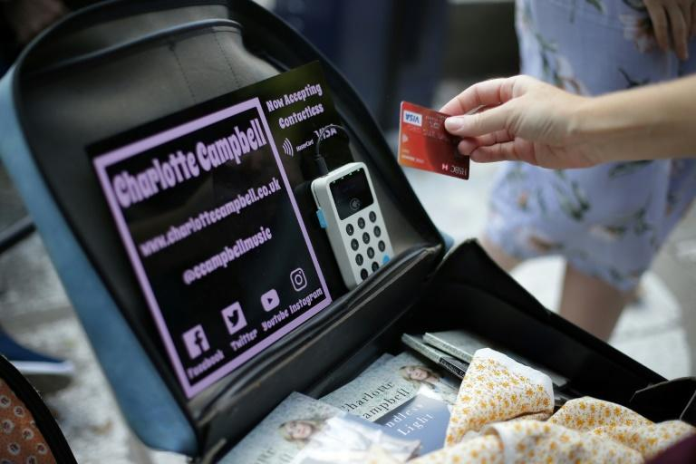 In a growing trend, busker Charlotte Campbell uses her phone to enable people to tap their bank cards on her contactless card reader to make donations