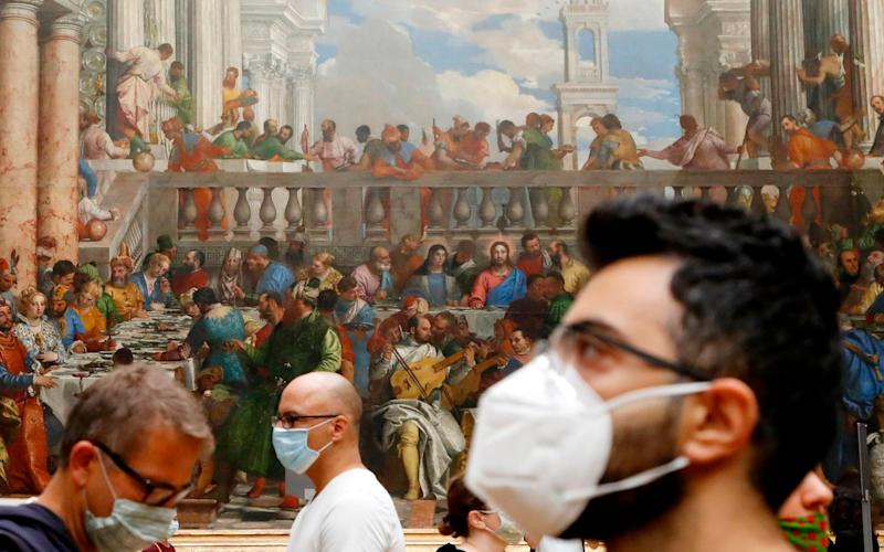 "Visitors wearing face mask stands in front of ""The Wedding Feast at Cana"" oil on canvas painting by the Italian artist Paolo Veronese - AFP"