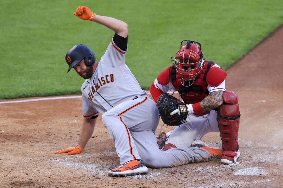 San Francisco Giants' Darin Ruf, left, is tagged out by Cincinnati Reds' Tucker Barnhart, right, at home plate during the fifth inning of a baseball game in Cincinnati, Tuesday, May 18, 2021. (AP Photo/Aaron Doster)