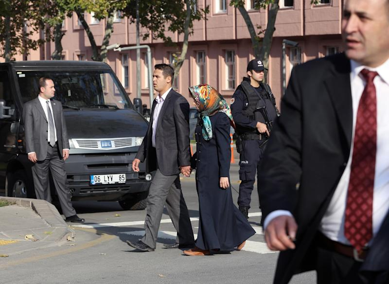 A couple walk by as security officials close a road leading to Turkish Prime Minister Recep Tayyip Erdogan's office, in the background, shortly after police subdued a man who was carrying a fake bomb in Ankara, Turkey, Thursday, Nov. 21. 2013. Police fired two warning shots in the air before overpowering and arresting him, said an aide to the prime minister. The 53-year-old man, identified as Tugrul B., was carrying a device made to look like a bomb, the official said. He was being questioned and the motive for his action was not immediately known.(AP Photo/Burhan Ozbilici) (AP Photo/Burhan Ozbilici)
