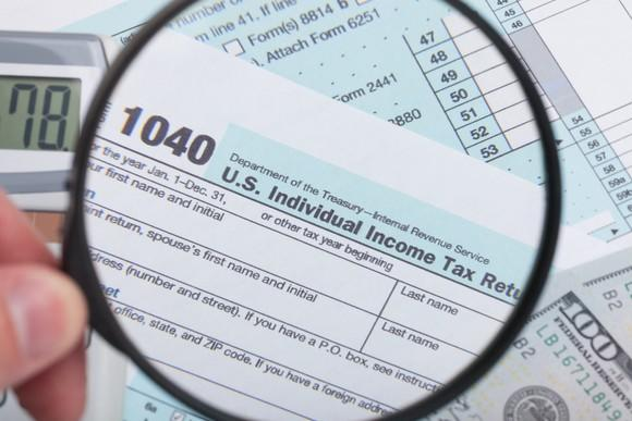 A magnifying glass being held over IRS tax form 1040.