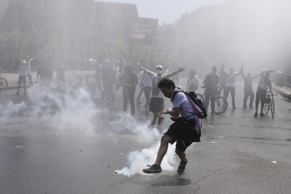 A protester kicks a tear gas canister during clashes with police in Santiago, Chile, Sunday, Oct. 20, 2019. Protests in the country have spilled over into a new day, even after President Sebastian Pinera cancelled the subway fare hike that prompted massive and violent demonstrations. (Photo: Esteban Felix/AP)