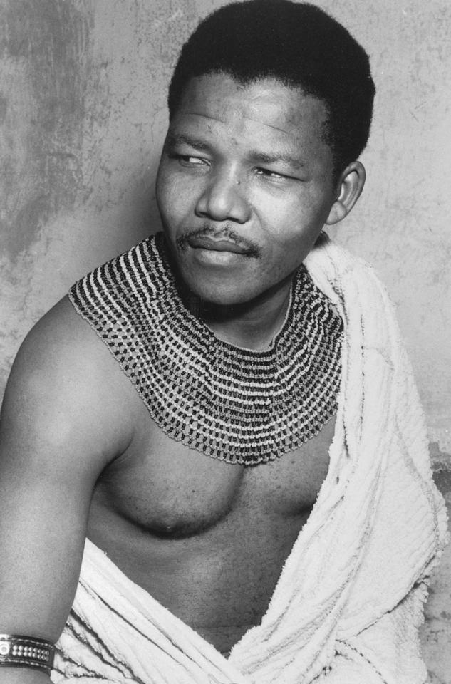 <p>Mandela wearing traditional beads and a bed spread during his time in hiding from the police in South Africa in 1961.</p>